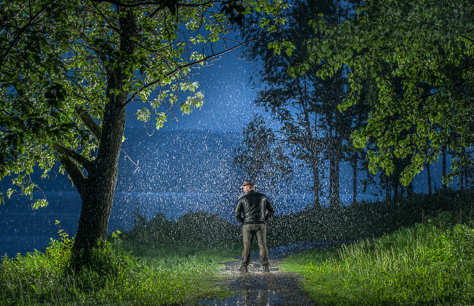 Backlit raindrops on a lonely man illustrating rain photography
